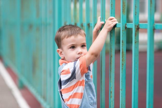 Un garçon sur le terrain de jeu une grande clôture verte une clôture avec de la peinture écaillée