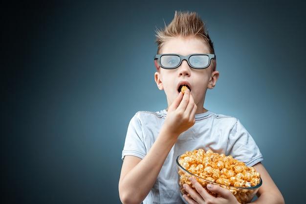 Le garçon tient dans ses mains et mange du pop-corn en regardant un film dans des lunettes 3d, mur bleu. le concept de cinéma, films, émotions, surprise, loisirs. plateformes de streaming.