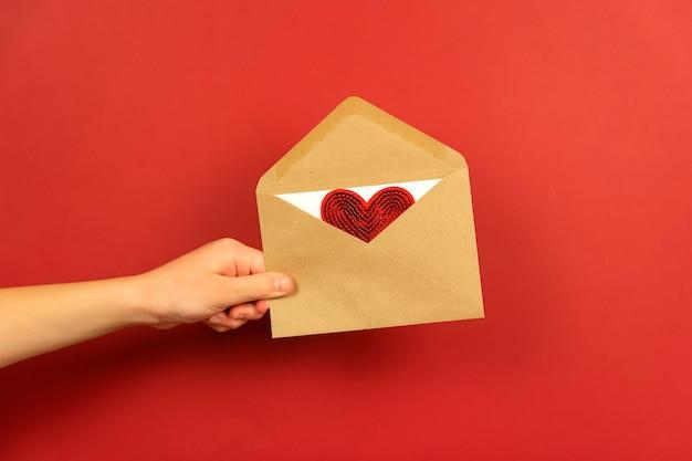 Un garçon tient une enveloppe avec une lettre d'amour et un cœur rouge dedans