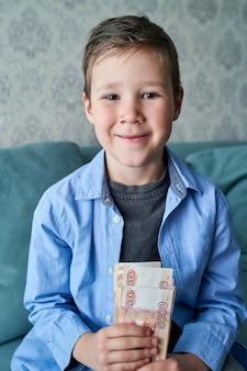 Le garçon tient une liasse de billets de cinq mille dollars russes dans ses mains.