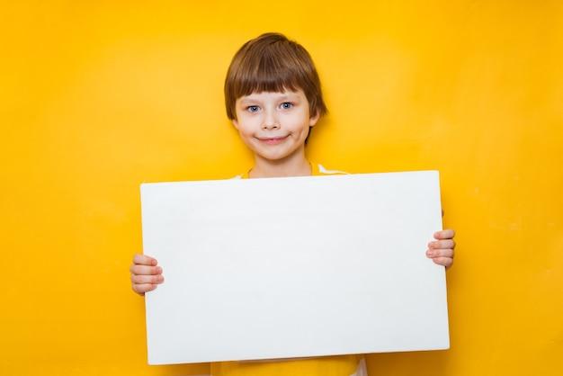 Garçon tient une pancarte blanche