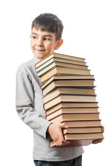 Garçon tient une pile de vieux livres et souriant