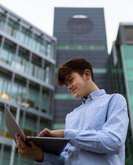 Garçon de tir moyen tenant un ordinateur portable