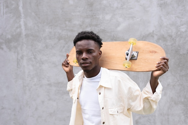 Garçon de tir moyen tenant le skate
