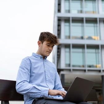 Garçon de tir moyen travaillant avec un ordinateur portable