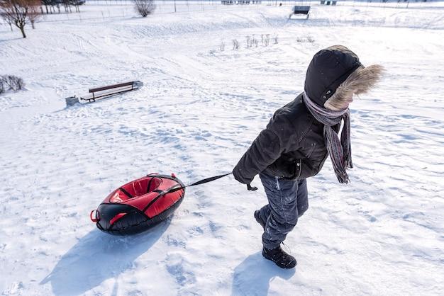 Le garçon tire un tube en hiver