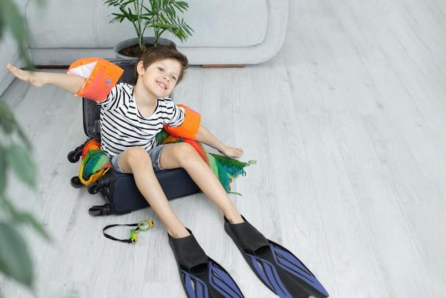 Garçon de touriste avec une valise et des palmes reste à la maison.