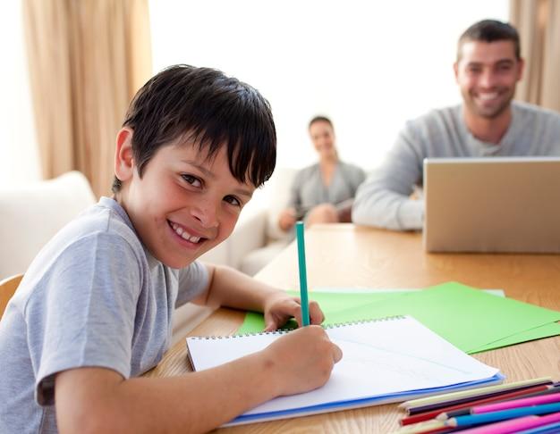 Garçon en train de peindre et parents travaillant à la maison