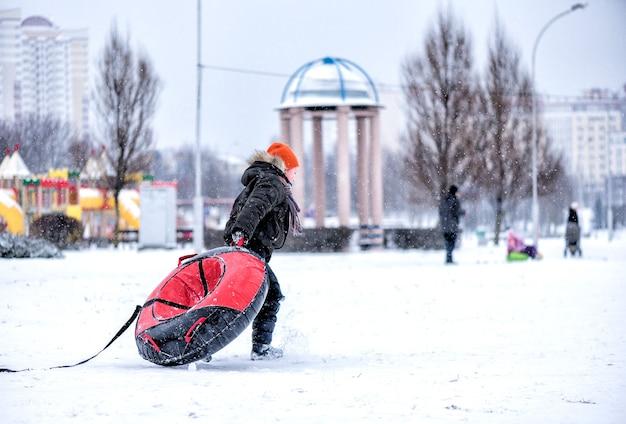 Le garçon traîne un tube le long d'un parc à neige