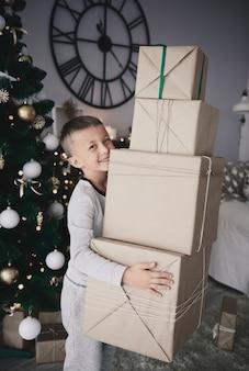 Garçon transportant une pile de cadeaux