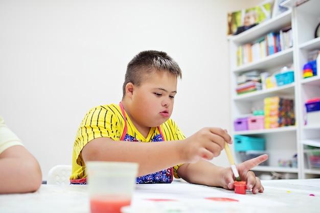 Garçon trisomique dessiner à une table