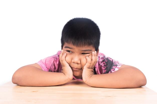 Garçon triste assis seul à une table en bois, noir et blanc