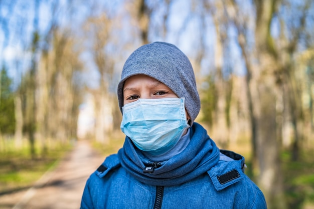 Garçon triste dans un masque médical protecteur extérieur