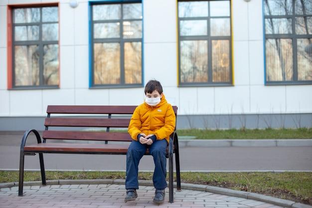 Garçon triste dans une veste jaune dans un masque médical blanc assis sur un banc dans la rue