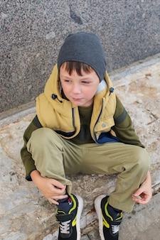 Garçon triste et ennuyé de 5 à 6 ans dans un parc de la ville