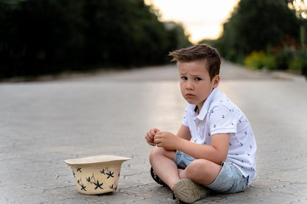 Un garçon triste est assis par terre et demande