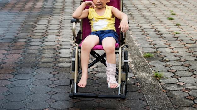 Garçon triste avec une jambe cassée sur plâtre en fauteuil roulant