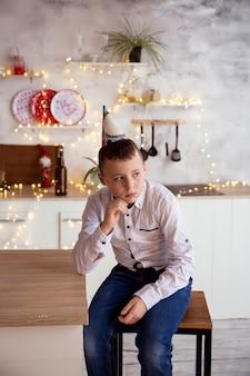 Le garçon triste s'assied dans la cuisine