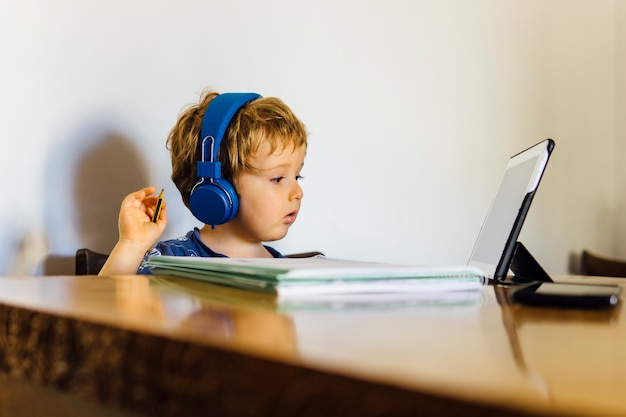 Garçon de trois ans assistant à un cours en ligne à l'école connecté à la tablette à la maison en regardant les médias