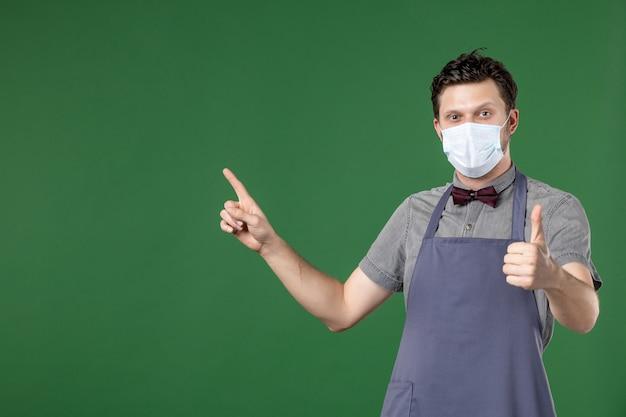 Garçon en uniforme avec masque médical et pointant vers le côté droit faisant un geste correct sur fond vert