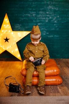 Garçon en uniforme militaire russe avec caméra. garçon jouant au soldat.