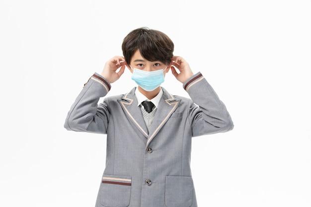 Garçon en uniforme scolaire portant un masque