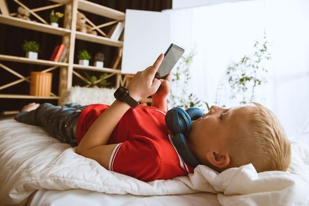 Garçon utilisant différents gadgets à la maison. petit modèle avec montres connectées, smartphone ou tablette et écouteurs. faire des selfies, discuter, jouer, regarder des vidéos. interaction des enfants et des technologies modernes.