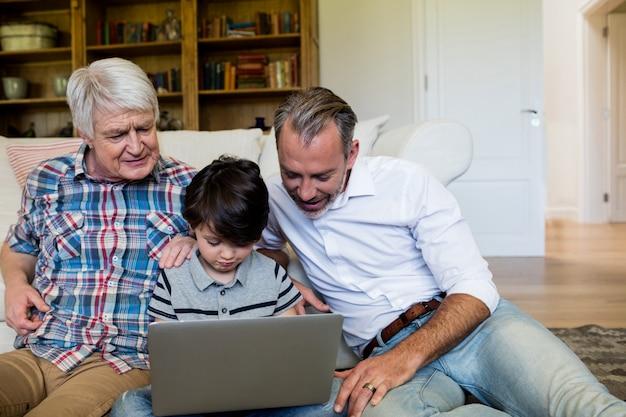 Garçon utilisant un ordinateur portable avec son père et son grand-père dans le salon