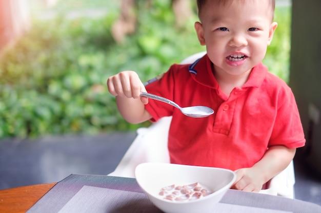 Un garçon utilise une cuillère pour manger des céréales pour le petit déjeuner