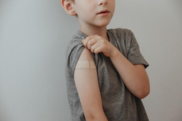 Garçon vacciné montrant le bras après l'injection du vaccin covid-19