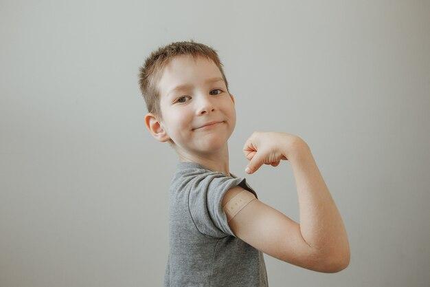 Garçon vacciné montrant le bras après l'injection du vaccin covid19