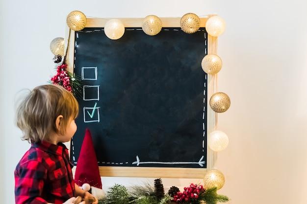 Un garçon vérifiant les options sur un tableau noir avec fond