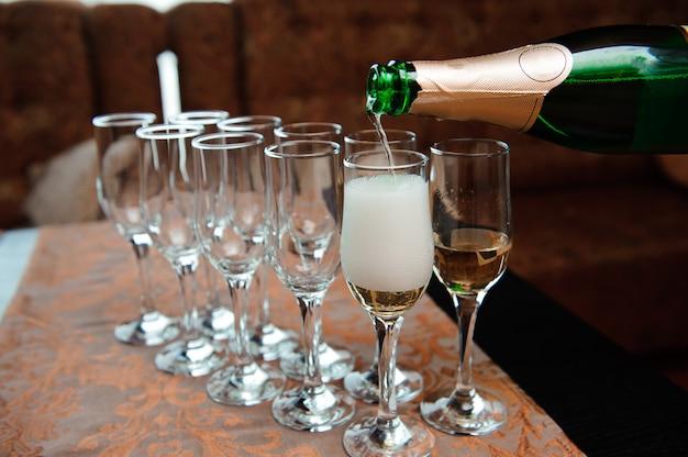 Garçon verse du champagne dans des verres, événement de luxe.