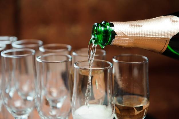 Garçon verse du champagne dans des verres sur la table