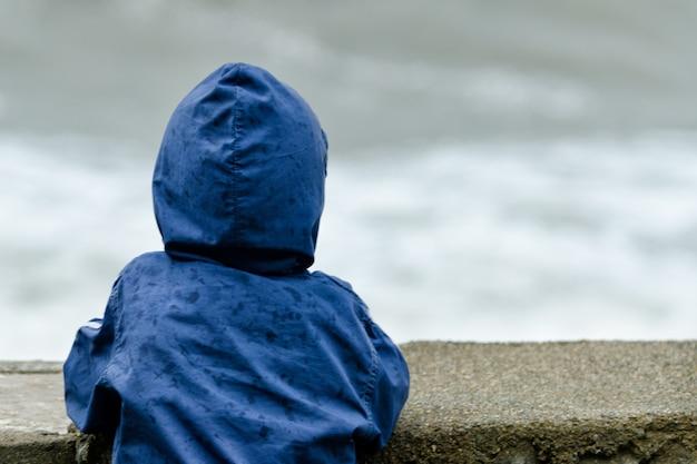 Garçon en veste bleue avec capuche se tient avec son dos. jetée contre les vagues de la mer