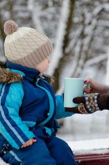 Garçon en vêtements d'hiver prenant une tasse de mains féminines sur fond d'arbres enneigés