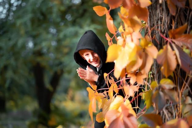 Un garçon vêtu de noir se tient près d'un arbre sur lequel pendent des feuilles d'automne jaunes