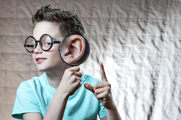 Un garçon vêtu d'un t-shirt léger penchait sa patte contre son oreille, à partir de laquelle il s'était fortement développé