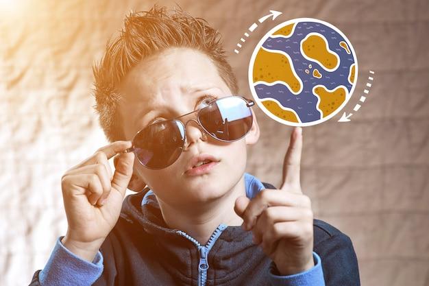 Un garçon vêtu d'une veste de sport tourne sur son globe terrestre peint du doigt, choisissant l'endroit où partir en voyage
