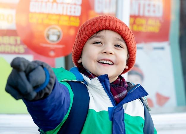 Garçon avec visage souriant, pointant son doigt