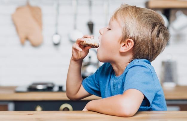 Garçon vue de côté manger un cookie