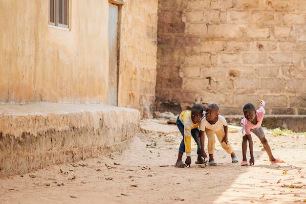 Garçons africains tir complet jouant ensemble