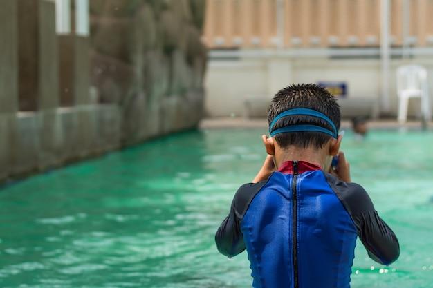 Les garçons asiatiques nagent dans la piscine.