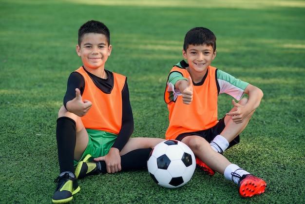 Garçons assis sur un terrain de football