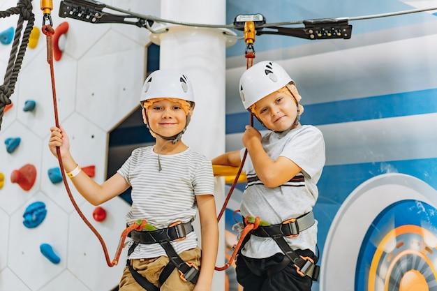 Garçons caucasiens de 7-8 ans s'élevant dans le parc d'aventure passant le parcours du combattant. parc d'accrobranche à l'intérieur. photo de haute qualité