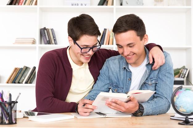 Garçons de classe assis à table et livre de lecture en classe