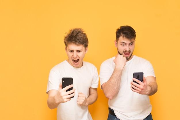 Garçons dans un t-shirt blanc sur jaune avec des smartphones dans leurs mains