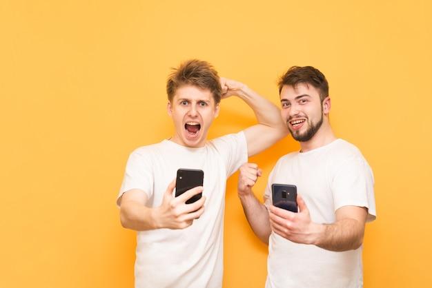 Garçons émotifs, tenant un smartphone dans leurs mains, portant des t-shirts blancs, se réjouissant d'une victoire sur le jaune