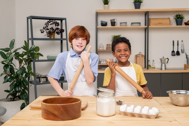 Garçons enveloppés dans la lecture d'une recette à l'aide d'une tablette numérique tout en se tenant à une table de cuisine en bois afin de faire une surprise pour la fête des mères, portrait