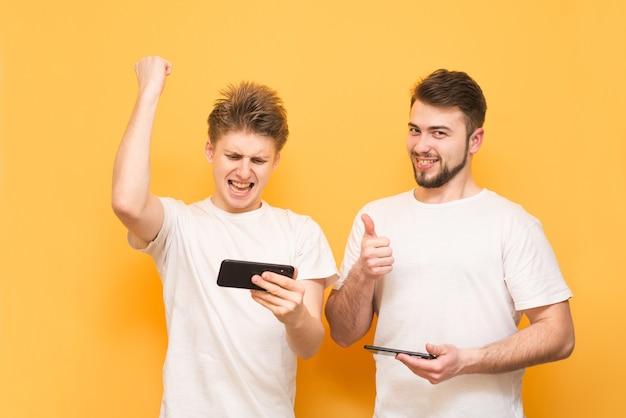 Les garçons extrêmes jouent émotionnellement à des jeux sur smartphone, debout sur jaune